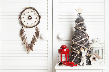 Brown cream dream catcher , red and white candlesticks and wooden christmas tree on white door background. Christmas decoration and copy space for text Stock Photo