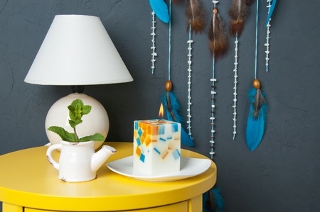Turquoise dream catcher close up, yeliow nightstand , table lamp and aroma candle on gray textured background. Texture of concrete.