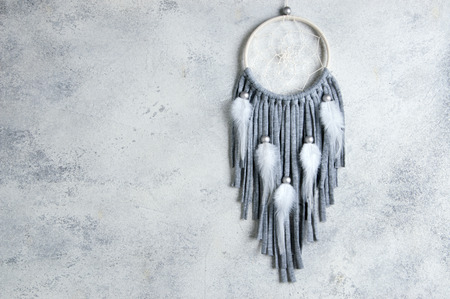 Beige gray dream catcher on white gray textured background. Texture of concrete, copy space for text. Stock Photo