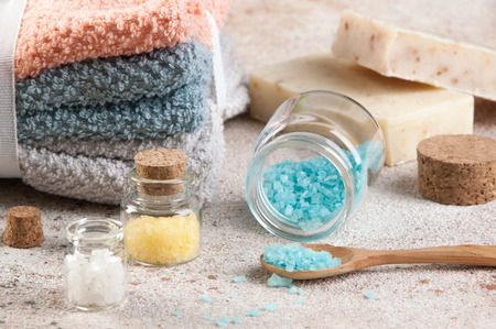 Bath salts in glass bottles,wooden spoon, towels and handmade soap on concrete background. Spa setting.
