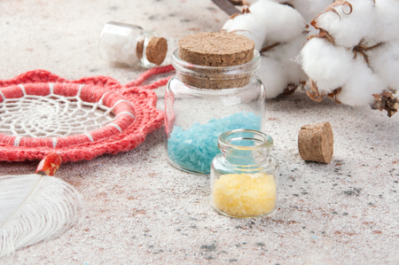 Coral dreamcatcher and bath salts in glass bottles on concrete background. Copy space for text. Standard-Bild
