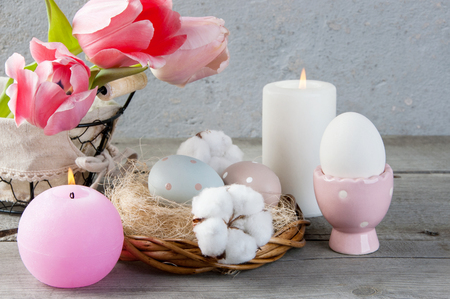 Eggs, pink tulips and aroma candles on old wooden background. Copy space for text, Ester decorations Stock Photo