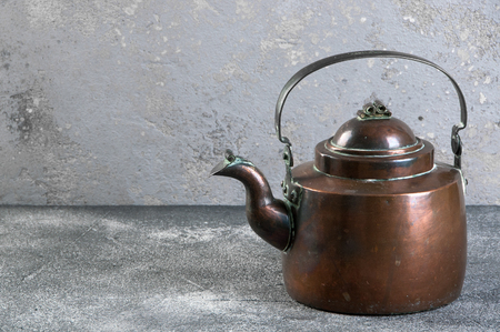 Antique copper teapot on gray concrete background.