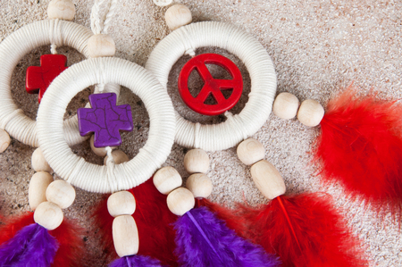Bright dream catchers with crosses , sing peace and red violet feathers on a concrete background. Copy space for text.