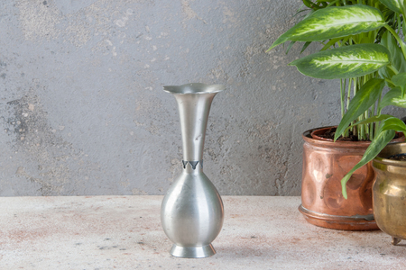 Vintage pewter vase and green plants in brass flower pots on concrete background. Copy space for text.