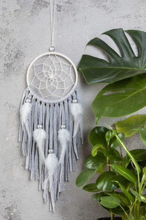 Gray beige dream catcher in bedroom interior on aquamarine textured background. Bedroom decor