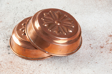 Vintage copper cake molds close up on a concrete background. Copy space for text.