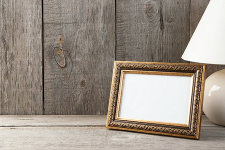 Empty brass picture frame and table lamp on old wooden gray textured background. Home decor and copy space for text.
