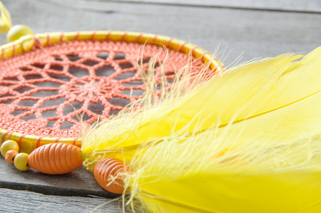 Orange yellow dream catcher on wooden gray background. Copy space for text.