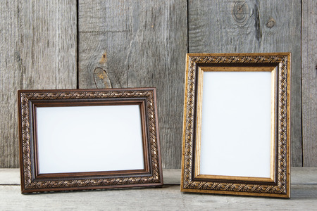 Two empty picture frames on old wooden gray textured background. Home decor and copy space for text.