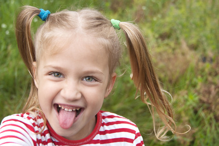 Сheerful cute blonde girl with ponytails shows tongue close up on the background of green grass. Copy space for text.