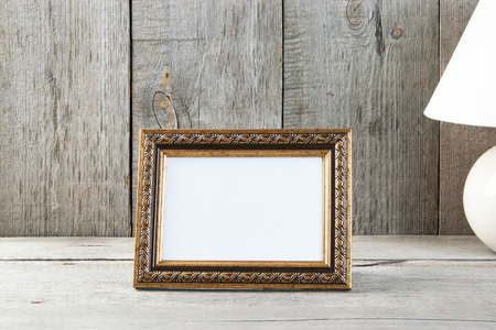 Empty picture frame and table lamp on old wooden gray textured background. Home decor and copy space for text.