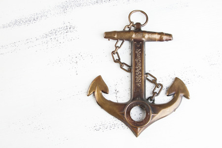 Vintage brass anchor on shabby white wooden background. Copy space for text.