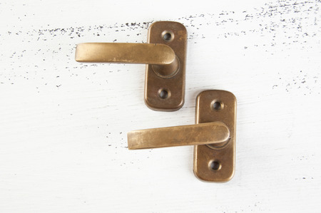Vintage bronze window handles on shabby white wooden background. Copy space for text.