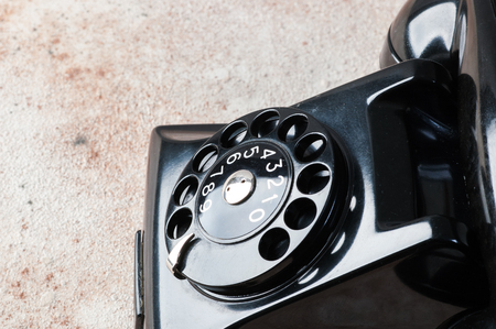 Antique black rotary phone on concrete background. Copy space for text.