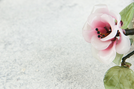Pink glass flower on concrete background. Copy space for text. 写真素材
