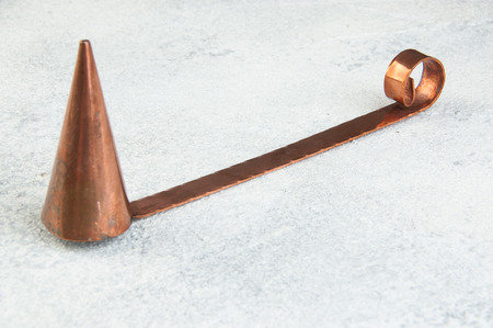 Antique copper candle snuffer on concrete background. Copy space for text. Stock Photo