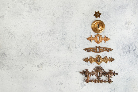 Vintage antique bronze keyhole covers lined up in the shape of a Christmas tree close up on concrete background. Christmas decorations.