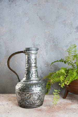 Vintage metal vase and green plant in copper vintage flower pot on a concrete background. Copy space for text.