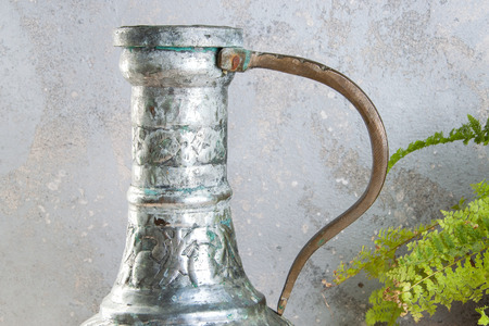 Vintage metal jug with handle close up on a concrete background. Copy space for text.
