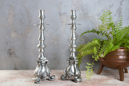 Vintage pewter candlesticks and green plant in copper vintage flower pot on a concrete background. Copy space for text.