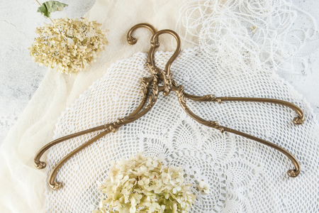 Vintage brass clothes hangers on crochet doily background. Copy space for text. 版權商用圖片