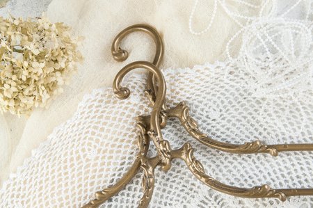 Vintage brass clothes hangers close up on crochet doily background. Copy space for text.