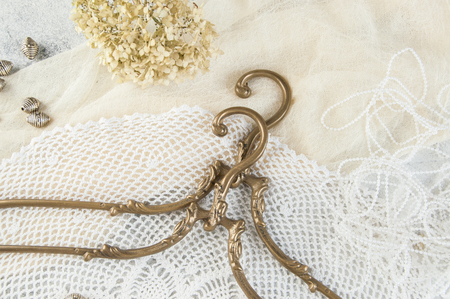 Vintage brass clothes hangers close up on crochet doily background. Copy space for text. Banque d'images - 119573065