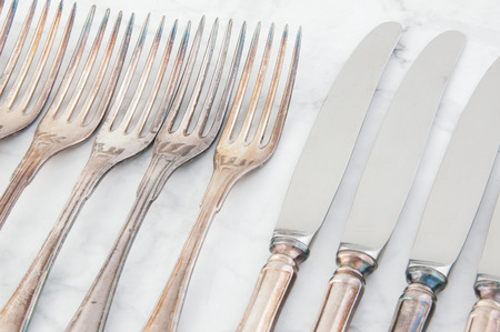 Vintage knives and forks close up on white gray background. Copy space for text.