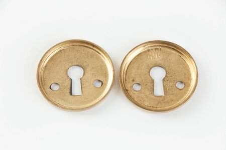 Vintage brass keyhole lock covers on white background. Copy space for text.
