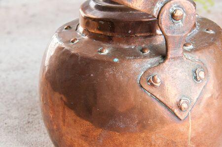Antique copper kettle close up on concrete background. Copy space for text.