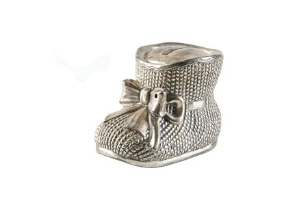 Antique metal money box in the shape of a bootie with bow isolated on white background