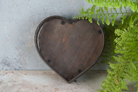 Antique brown basket shape of the heart on concrete background. Copy space for text.