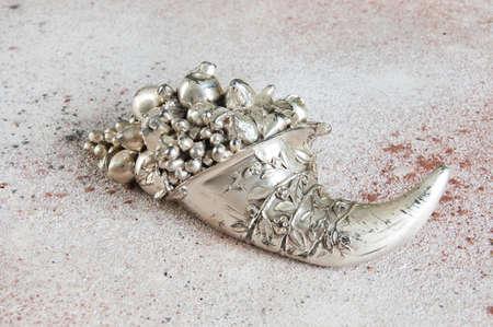 Vintage horn of cornucopia in silver plated symbol of prosperity on concrete background. Copy space for text.