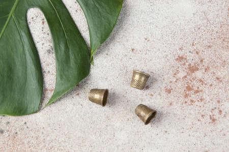 Antique brass thimbles on concrete background. Copy space for text. Banque d'images