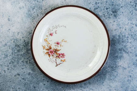 Antique porcelain plate on concrete background. Copy space for text, food photography props.