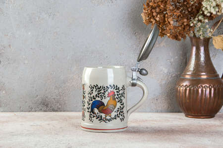 Collectible vintage ceramic beer mug with pewter lid and colorful rooster on a concrete background. Copy space for text.