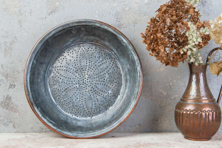 Antique copper sieve and composition of dried flowers in vintage copper jug on concrete background. Copy space for text.