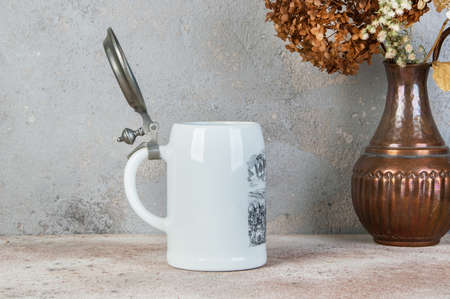 White collectible vintage ceramic beer mug with pewter lid  on a concrete background. Copy space for text.