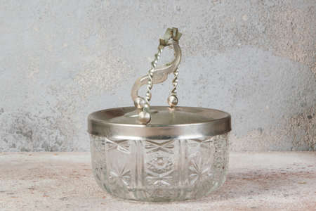 Old glass sugar bowl with metal lid. Soviet vintage, kitchen decor, copy space for text.