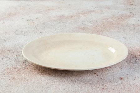Antique porcelain oval plate on concrete background. Copy space for text, food photography props. Foto de archivo