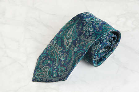 Blue neck tie with pattern on marble background. Copy space for text.
