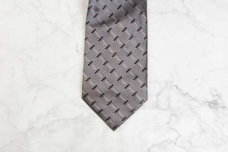 Gray neck tie on marble background. Copy space for text.