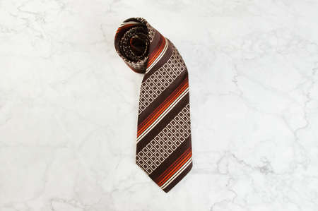 Brown neck tie with geometric pattern on marble background. Copy space for text. Foto de archivo