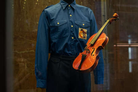 old ancient violin suspended in air next to a blue historic uniform Reklamní fotografie