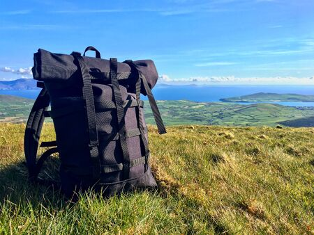 beautiful view: black fashion backpack on a green meadow with blue sky and ocean in the background 스톡 콘텐츠
