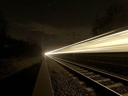 Focused night rails in the dark and blurry passing train. Night photo. Studenka. Czech Republic.