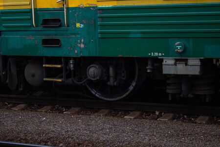 Detail of a green train chassis on rails at a train station.