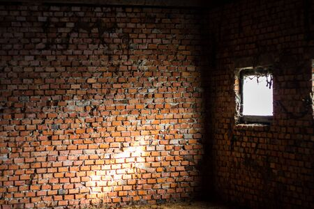 Detail of an ancient red brick wall slightly bleached with salt. Fragments of the narrow white stone windows. The bricks were blocked by metal tie rods. Background use.