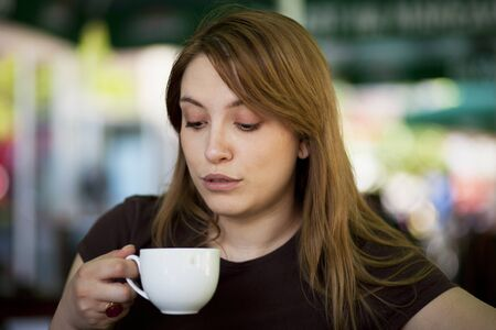 Young woman drinking hot beverage in a restaurant